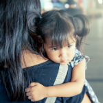 Mother holding child representing crime victims and VAWA for Denver immigration firm Shaftel Law